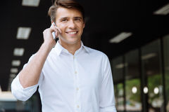 Cheerful young businessman talking by cell phone on the street Royalty Free Stock Photo