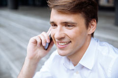 Cheerful young businessman talking on mobile phone Stock Photo