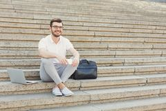 Cheerful young businessman using phone and laptop on stairs. Smiling businessman in eyeglasses is holding his cell phone while sitting between laptop computer Royalty Free Stock Images