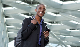 Cheerful young businessman walking with bag and mobile phone Royalty Free Stock Photos