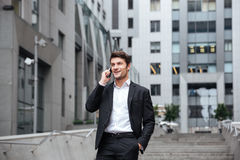 Cheerful young businessman walking and talking on cell phone Royalty Free Stock Photos
