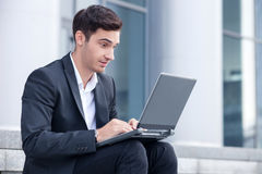 Cheerful young businessman is working with Royalty Free Stock Photos