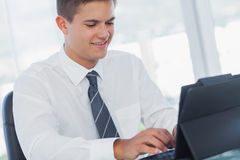 Cheerful young businessman working on his tablet pc Stock Photos