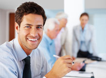 Cheerful young businessman working at office Stock Image