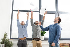Cheerful young businessmen triumphing and throwing papers in office Royalty Free Stock Photo