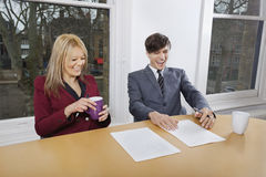 Cheerful young businesspeople with coffee mugs and documents at conference table Royalty Free Stock Photography