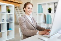 Young analyst. Cheerful young businesswoman computing by workplace while making analysis or research of online data stock image