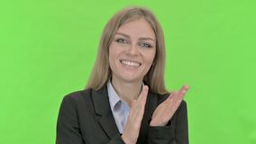 Cheerful young businesswoman doing clapping against chroma key stock footage