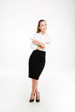 Cheerful young businesswoman pointing finger away and looking at camera Stock Photography
