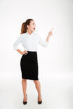 Cheerful young businesswoman pointing finger away Stock Photos