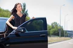 Cheerful young businesswoman is preparing to sit. Attractive woman is ready to drive her car. She is opening the door and staying behind it. The girl is smiling Stock Photography