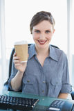 Cheerful young businesswoman presenting disposable cup Stock Photo