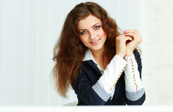 Cheerful young businesswoman sitting at the table and looking Royalty Free Stock Photography
