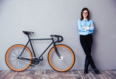 Cheerful young businesswoman standing near bicycle Royalty Free Stock Image