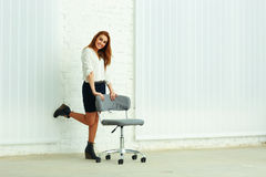 Cheerful young businesswoman standing near the chair Royalty Free Stock Photography