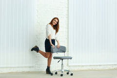 Cheerful young businesswoman standing near the chair Stock Image