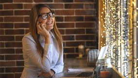 Cheerful young businesswoman talking on the phone in a cafe. Businesswoman talking on the phone and laughing stock footage