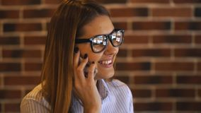 Cheerful young businesswoman talking on the phone in a cafe. Businesswoman talking on the phone and laughing stock video