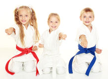 Cheerful young children to sit in a ceremonial kimono karate pose and hit a punch Royalty Free Stock Photo