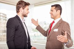 Cheerful young colleagues are greeting each other Royalty Free Stock Photos