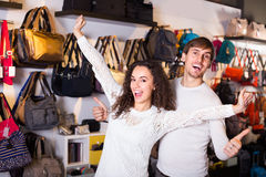 Cheerful young couple in bags shop Royalty Free Stock Image