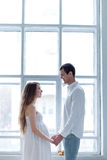 Cheerful young couple dressed in white sitting on royalty free stock photography