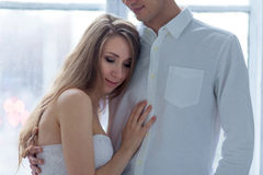 Cheerful young couple dressed in white sitting on stock images