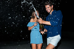 Cheerful young couple drinking champagne and having fun at night. On the beach stock photography