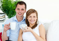 Cheerful young couple drinking coffe on the sofa Stock Images