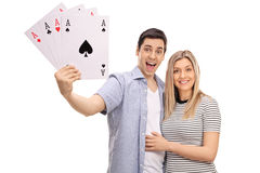 Cheerful young couple with four aces playing cards Royalty Free Stock Image