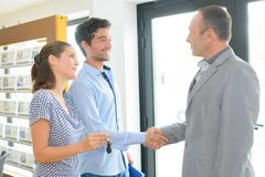 Cheerful young couple handshaking after successful transaction stock photos