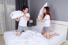 Cheerful young couple having a pillow fight on bed Stock Images