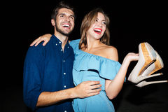 Cheerful young couple hugging and having fun at night. Cheerful young couple with shoes in hands hugging and having fun at night stock images