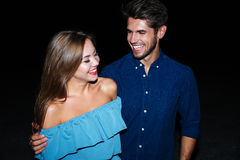 Cheerful young couple hugging and laughing together. At night stock image