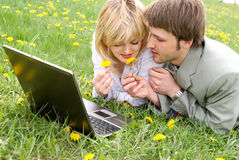 Cheerful young couple with laptop outdoors royalty free stock image