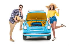 Couple with luggage standing by car. Cheerful young couple with luggage standing by car with open bonnet isolated on white Stock Photos
