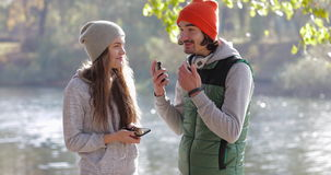 Cheerful Young Couple Man And Pretty Talking Woman Using Cell Smart Phone Outdoor Sunrise, Morning Autumn Park stock footage
