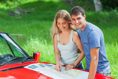 Cheerful young couple reading map on their cabriolet bonnet Stock Image