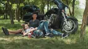 Positive teenage couple relaxing outdoor near bike stock video footage