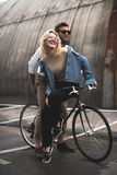 Cheerful young couple riding bicycle on parking place Royalty Free Stock Image