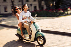 Cheerful young couple riding a scooter Stock Photo
