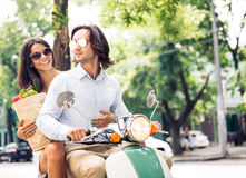 Cheerful young couple riding a scooter Stock Photos