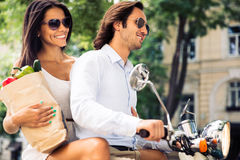 Cheerful young couple riding a scooter Stock Image