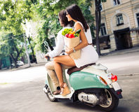 Cheerful young couple riding a scooter Royalty Free Stock Photography