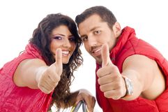 Cheerful young couple showing thumbs up. On an isolated white background Royalty Free Stock Photo