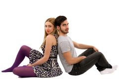 Cheerful young couple sitting with back to each other on floor, Stock Images