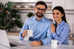 Cheerful young couple sitting in the kitchen stock photo