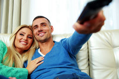 Cheerful young couple sitting on the sofa Royalty Free Stock Photo