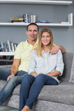Cheerful young couple sitting on their couch Royalty Free Stock Photos