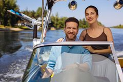 Cheerful young couple smiling while sailing a motorboat. Unforgettable experience. Upbeat young couple smiling widely while sailing a motorboat together during stock photo